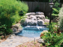 Combination pool and spa with waterfall in an inviting garden setting