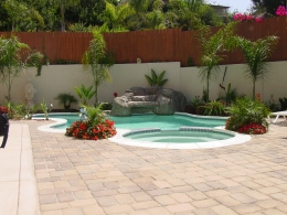 Free form design with white safety grip coping, spa, deck pavers and rock waterfall