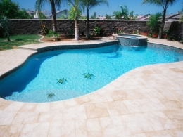 Free form pool with paver decking, raised spa with spillover, and tile mosaic