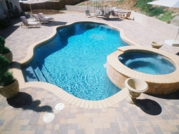 Free form pool with raised spa, tan bullnose brick coping, paver decking and medium gray plaster