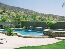 Free form raised pool with ledgerstone, quartzite coping, raised spa, sheer descent waterfalls, and colored concrete deck