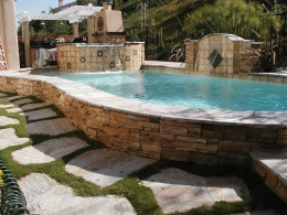 Raised pool and spa with ledger stone and sheer descent water feature