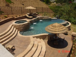 Vanished edge pool with raised spa, sheer descents, thatch palapa, and swip up barstools